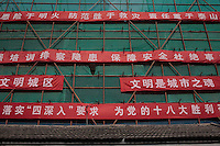 "Public slogans on construction site in a hutong of beijing (Shatan hutong) calling people to take care to security, to adopt a ""civilized"" behaviour "", and celebrate the 18 great victories of the PCC. 4 august 2012"