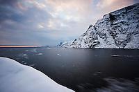 Snow covered mountains rise from sea, Å I Lofoten, Lofoten Islands, Norway