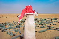 An Arab man gesticulates at discarded shells, from which explosive material is extracted to made improvised bombs.