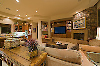 Contemporary family room in neutral colors with couch in front of fire place and flat screen TV