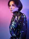 Fashion photo of a beautiful woman wearing a black necklace and a fancy black blouse in colored blue purple light