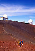 Hikers approach the summit of Mauna Kea, Big Island of Hawaii with astronomical observatories in the background.