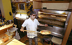 Pizza chief Agostino Trentacoste pulls a pizza pie out of the oven at the La Vita E' Bella Pizzera on 2nd Avenue. They specialize in home made thin-crusted Italian pizzas.  Jim Bryant Photo. ©2010. All Rights Reserved.
