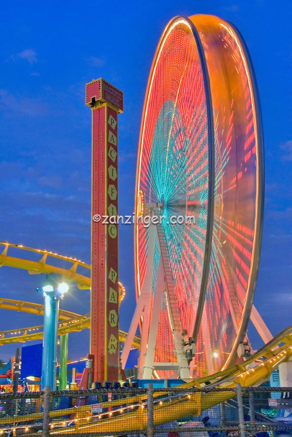 Santa Monica CA Pacific Pier Ferris Wheel,streaking, Beautiful Sunset, family amusement park large New Pacific Ferris wheel Roller Coaster moving over the ocean High dynamic range imaging (HDRI or HDR)