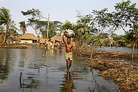 A man carries belongings through the floodwaters. Thousands of people were displaced in Shyamnagar Upazila, Satkhira district after Cyclone Aila struck Bangladesh on 25/05/2009, triggering tidal surges and floods..