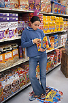 Berkeley, CA Latina girl fourteen years old studying nutritional information on cereal box in supermarket  MR