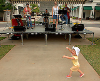 A young girl dances to the music during an outdoor concert. Photo was taken during the annual Fourth of July Celebration and community parade in Birkdale Village in Huntersville, NC. Birkdale Village combines the best of shopping, dining, apartments and entertainment venues within a 52-acre mixed-use development.