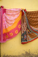 """Sari on the wall,Jaisalmer the old City and fort.J a i s a l m e r   J a i s a l m e r  n i c k n a m e d   """" T h e   G o l d e n   C i t y """" ,   i s   a   t o w n   i n   t h e   I n d i a n   s t a t e   o f   R a j a s t h a n .   T h e   t o w n   s t a n d s   o n   a   r i d g e   o f   y e l l o w i s h   s a n d s t o n e ,   c r o w n e d   b y   a   f o r t ,   w h i c h   c o n t a i n s   t h e   p a l a c e   a n d   s e v e r a l   o r n a t e   J a i n   t e m p l e s .   M a n y   o f   t h e   h o u s e s   a n d   t e m p l e s   a r e   f i n e l y   s c u l p t u r e d .   I t   l i e s   i n   t h e   h e a r t   o f   t h e   T h a r   D e s e r t   a n d   h a s   a   p o p u l a t i o n   o f   a b o u t   7 8 , 0 0 0 .   I t   i s   t h e   a d m i n i s t r a t i v e   h e a d q u a r t e r s   o f   J a i s a l m e r   D i s t r i c t ....Jaisalmer Fort is one of the largest of desert forts of the world. It is situated in Jaisalmer city in Indian state of Rajasthan. It was built in 1156 AD by the Bhati Rajput ruler Rawal Jaisal, from where it derives it name. The fort stands proudly admist the golden stretches of the great Thar Desert, on Trikuta Hill and had been the scene of many battles. Its massive yellow sandstone walls are a tawny lion color during the day, turning to a magical honey-gold as the sun sets and camouflages the fort making it appear a part of the picturesque yellow desert. Thus, it is also known as the """"Golden Fort"""".."""