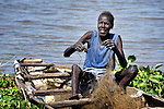 A man repairs his fishing net beside the Upper Nile River in Malakal, Southern Sudan.