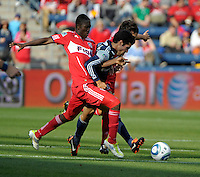 Chicago forward Patrick Nyarko (14) and midfielder Baggio Husidic (9) collapse on New England midfielder Benny Feilhaber (22).  The Chicago Fire defeated the New England Revolution 3-2 at Toyota Park in Bridgeview, IL on Sept. 25, 2011.
