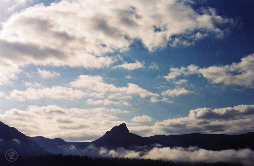 Mists hang over Lake Saint Clair with the silhouette of Cradle Mountain in the background from Tasmania's Overland Track.