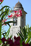 A church tower with pink flowers in the foreground in Oria, a town in the mountains on Lake Lugano, Italy.