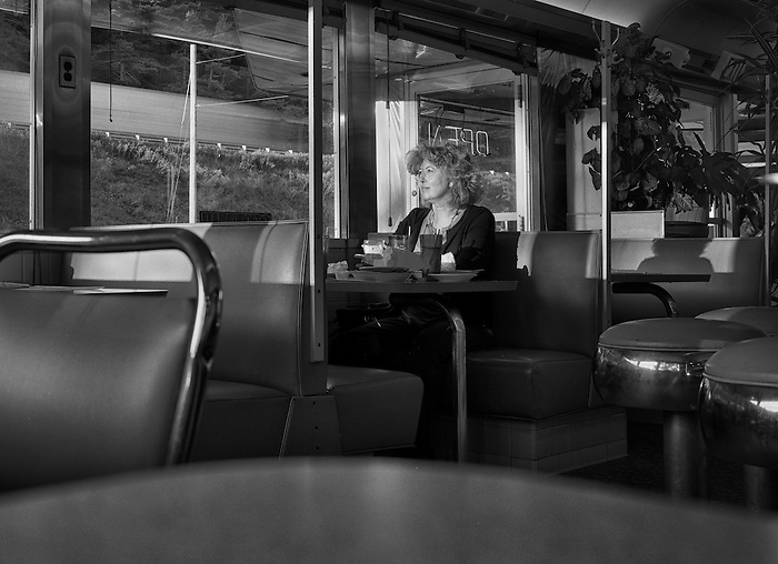 A woman sitting in a diner staring out the window.