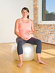 Pregnant woman (9 months) sits on a workout ball.