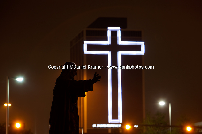 A statue of Jesus Christ in fron of a building-sized cross on the St. Joseph's Professional Building in downtown Houston.