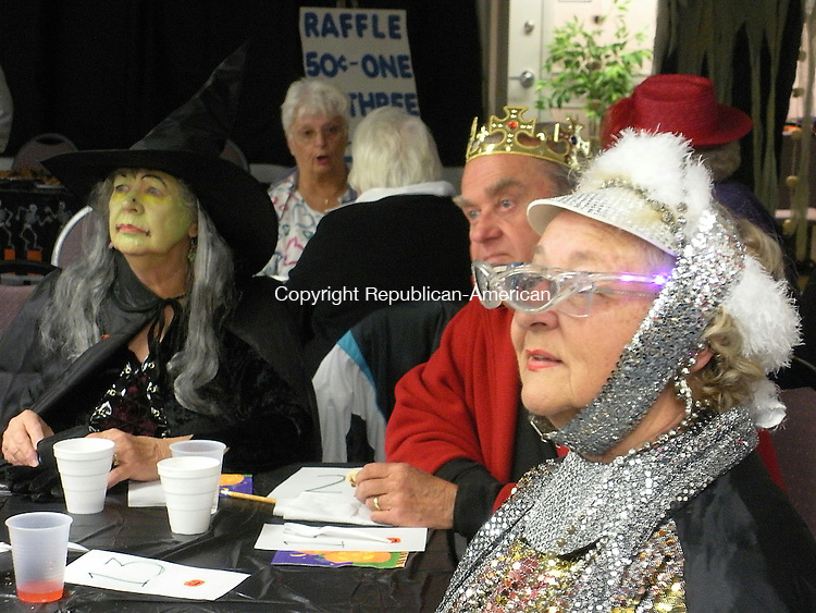 """HARWINTON, CT - 102908KB01 - 29 October 2008 - Gerry Stubbs of Burlington, right, and Priscilla and Fred Kunesch of Torrington wait for Harwinton Senior Center Director Sharlene Copeland to announce the winners in a costume contest during a Halloween party at the center on Wednesday. Stubbs, who was covered head-to-toe in sequined attire, won one of several prizes, as did Fred Kunesch, who was dressed up as a king. """"I don't know what I'm dressed up as,"""" Stubbs admitted. Kari Banach Photo"""