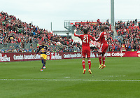 Toronto, Ontario - May 17, 2014: New York Red Bulls forward Thierry Henry #14 attempts a free kick as Toronto FC forward Jermain Defoe #18 and Toronto FC midfielder Jonathan Osorio #21 try to defend during a game between the New York Red Bulls and Toronto FC at BMO Field. Toronto FC won 2-0.