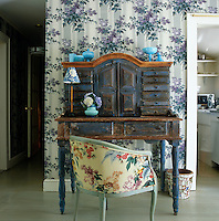 A Spanish Colonial-style desk stands in front of a wall in the living room