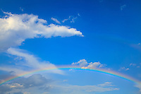 A classic rainbow appears against the backdrop of a partly cloudy blue sky.