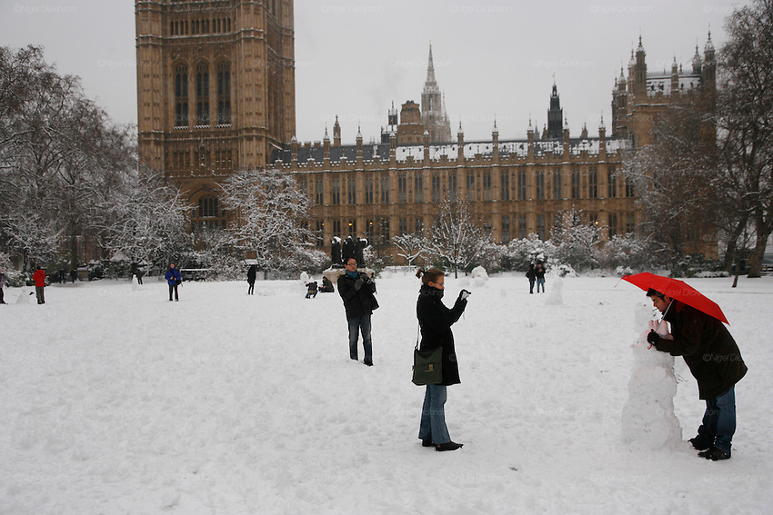Weather, climate change. London, Britain and Europe, is gripped by a big freeze. Winter conditions which are likened to Siberia swept across Europe, bringing traffic and transport to a halt, closing schools and stopping millions of people going to work. Whilst most buses and tubes were not working, some commuters and tourists got to central London to enjoy the freak snow.///People play making snowmen in Westminster gardens next to the Houses of Parliament