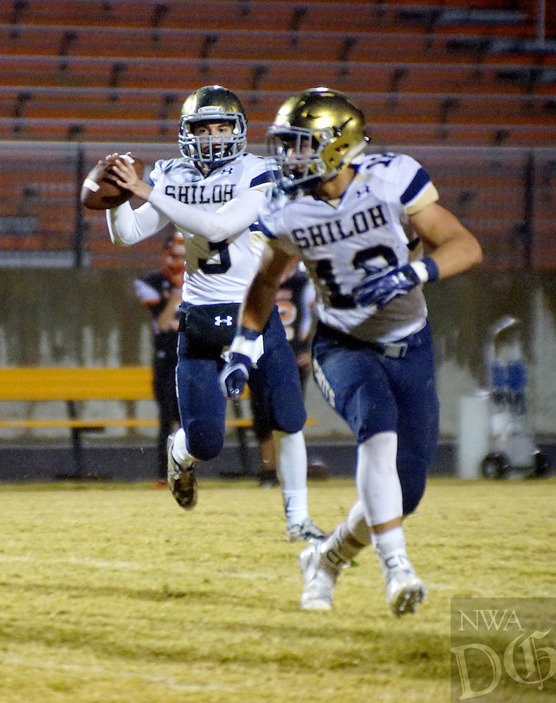 Photo by Randy Moll<br /> Connor Reece, Shiloh Christian's quarterback, looks for a receiver, with Broc Berus in the foreground, during play between Gravette and Shiloh Christian at Gravette on Friday, Oct. 30, 2015.
