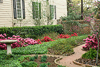 White clapboard house with landscaped side yard including curving brick walkways and blooming azaleas