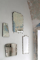 Fragments of contemporary mirror reflect the distressed paint effect on the walls of the living room