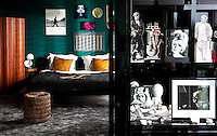 A view from the livng room into the bedroom, its colourful furnishings contrasting with the monochrome photographs on display in the shiny black bookcase by the doorway