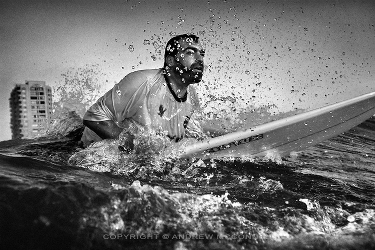 Awad Hania, brusts through the surf while paddling out to sea from Gaza City, in the Gaza Strip.