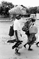 "Mozambique. Province of Gaza. Chokwe. The Limpopo river has flooded in february the whole town."" Local authorities, fearing a new flood, order the population to leave the town. Families flee with their belongings. The woman carries  a duck in her hand and a bag on her head. © 2000 Didier Ruef"