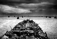Columns of troop-packed LCIs trail in the wake of a Coast Guard-manned LST en route for the invasion of Cape Sansapor, New Guinea.  The deck of the LST is closely packed with motorized fighting equipment.  1944. PhoM1c. Harry R. Watson. (Coast Guard)<br /> Exact Date Shot Unknown<br /> NARA FILE #:  026-G-2839<br /> WAR &amp; CONFLICT BOOK #:  1163