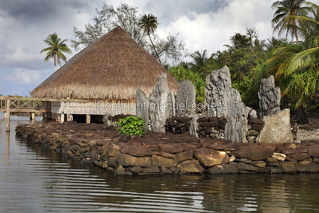 Marae Vaiotaha, a stone courtyard with platform and standing stones, built by a Polynesian civilisation and used as a ceremonial and religious site, and behind, Fare Pote'e, a reconstruction of a round communal dwelling, built on stilts with a thatched roof, on the banks of Lake Fauna Nui or Maeva Lake, at the archaeological site at Maeva village, on Huahine-Nui on the island of Huahine, in the Leeward Islands, part of the Society Islands, in French Polynesia. This marae is linked to the Fare Tou chiefdom and was used for worshipping ancestors and gods, and offerings were made here. They are thought to date from 13th - 15th centuries. The Fare Pote'e has been used as a house, meeting room, church, school and museum and has been rebuilt several times, most recently in 2000-01 by the Opu Nui Association. Maeva is thought to be an abandoned royal settlement, with many megalithic structures including marae, houses, agricultural structures, stone fish traps and fortification walls. Picture by Manuel Cohen