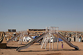 DOMIZ, IRAQ: A young girl stands near a slide in the Domiz refugee camp...Over 7,000 Syrian Kurds have fled the violence in Syria and are living in the Domiz refugee camp in the semi-autonomous region of Iraqi Kurdistan...Photo by Ali Arkady/Metrography