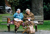 Elderly retired women sitting on a park bench and enjoying a picnic, England, UK