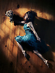 Young woman in a blue dress with a bouquet of wild flowers in a dynamic leap on wooden floor background, abstract artistic portrait in dramatic dim light