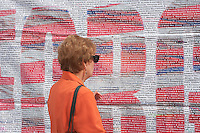 A woman reads the list of those who perished in the 9/11 terrorist attack of the World Trade Center.  The list is posted on Greenwich Street across from the entrance to the National September 11 Memorial.
