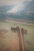 Daytime vertical view from the Sānménxiá Dam of a walkway on the Huang He and smokestacks at a power plant facility in the Sānménxiá Shì Húbīn District in Hénán Province.  © LAN