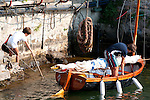 Two boys with their small wooden boat in Varenna, Italy on Lake Como