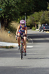 A female triathlete competes in a bicycle portion of a triathlon.