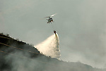 Fire fighting aircraft dropping water onto forest fire from suspended ballon,Costa del Sol, Andalucia, Spain