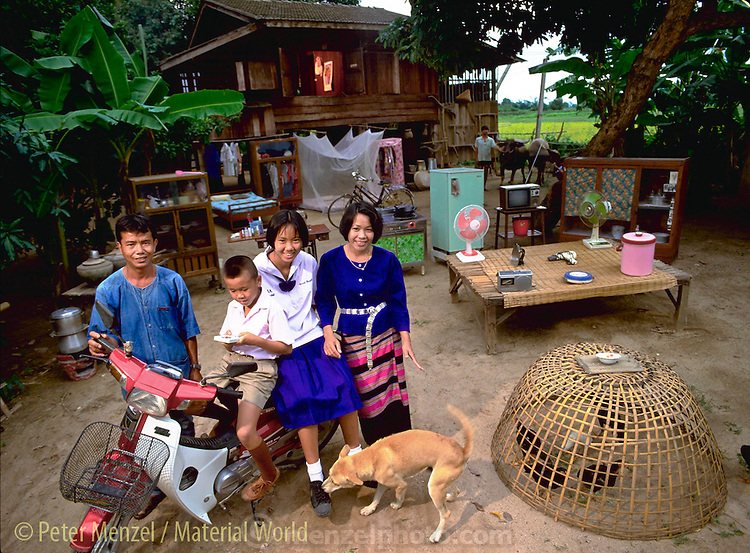 Tha.mw.01.xxs..The Kuenkaew Family, 5:30 pm, May 31 1993, in front of their home with all of their possessions, Ban Muang Wa, Thailand. Published in Material World, pages 80-81. {{Family members are: Boontham Khuenkaew (39, father); Buaphet Khuenkaew (35, mother); Jeeraporn Khuenkaew (14, daughter); Visith Khuenkaew (9, son); Vichai Sadub (Dang) (37, Buaphet's brother, seen here holding the family's water buffalos). (From Peter Menzel's Material World Project that showed 30 statistically average families in 30 countries with all their possessions). The Khuenkaews are a farming family that grows rice for personal use, and to sell for income. Buaphet's mother gave them the land on which to build their home. She and other family members live close by. The Khuenkaew's live in a wooden 728-square-foot house on stilts, surrounded by rice fields.}}.