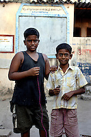 Two boys stop in the road holding a light bulb and wire on 21st Oct 2006.