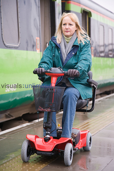 Woman driving electric mobility scooter alongside a train on a station platform. MR