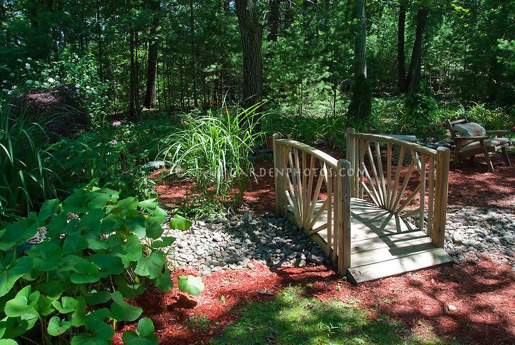 Dry stream river made from stones with wooden bridge with interesting shade patterns, sun and shade landscaping for a fake water garden feel, Miscanthus sinensis, chair furniture in dappled shade and sun