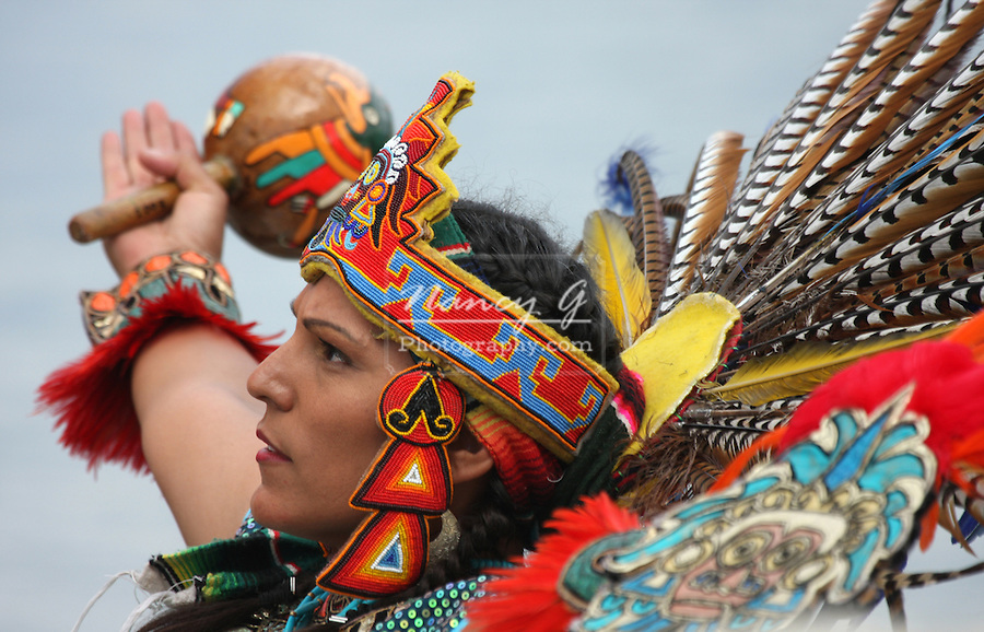 An Incan South American Indian in a fancy feather headdress with arms up in worship at the Milwaukee Lakefront Indian Summer Festival, Wisconsin