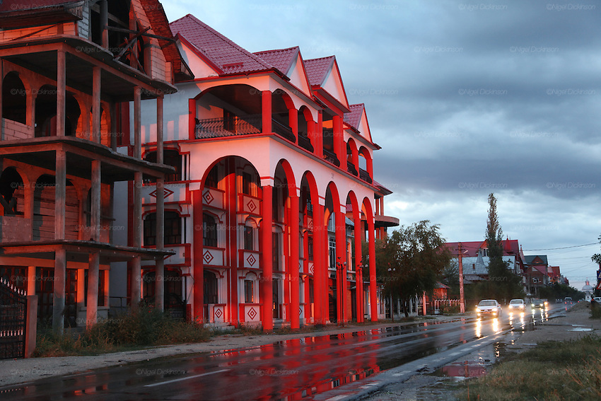 Rainstorm and early evening at Buzescu. Sumptuous homes for the Roma weathly. Extravagant decorated roofs, homes built like palaces with several floors and balconies, in all different shapes and colors, copying various architecrtural styles. Buzescu is a home for rich Roma and is well known for its typical Roma Gypsy style architecture. Buzescu lies northwest of Alexandria. Romania..Roma Gypsies left India 1000 years ago. Often nomadic. A collection of tribes with their own languages and culture, pushed by the Ottoman empire towards Europe, used and sold as mercenaries, slaves, prostitutes. They endured 500 years of slavery until mid 19th century. A million were killed in the holocaust. Hundreds of thousands exiled and refugees from kosovo. Many Eastern Europe Roma come to the west seeking a better life. They are shunned, marginalized, excluded. Both indigenous and foriegn Roma, whether European citizens or not, lack the opportunities of others, living on the periphery, in the brunt of racism, often deported back to their countries of origin.