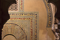 Detail of tesserae (glass mosaic with gold or coloured backing) with vegetal designs and kufic inscriptions on a horseshoe arch on the qibla wall next to the mihrab, in the Cathedral-Great Mosque of Cordoba, in Cordoba, Andalusia, Southern Spain. The first church built here by the Visigoths in the 7th century was split in half by the Moors, becoming half church, half mosque. In 784, the Great Mosque of Cordoba was begun in its place and developed over 200 years, but in 1236 it was converted into a catholic church, with a Renaissance cathedral nave built in the 16th century. The historic centre of Cordoba is listed as a UNESCO World Heritage Site. Picture by Manuel Cohen