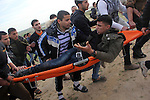 Palestinians carry a fellow protester wounded during clashes with Israeli forces near the  border with Israel, east of Jabalia refugee camp in northern Gaza Strip on January 31, 2014. The Israeli army fired live rounds and tear gas at protesters near the border fence, wounding seven Palestinians, medics said. Photo by Khaled al-Sabbah