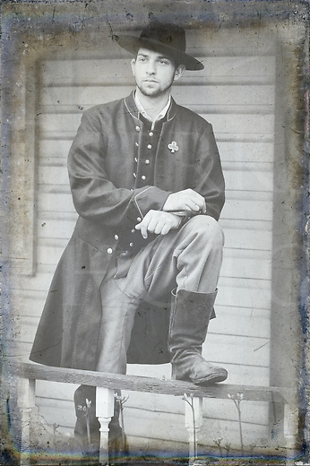 Soldier standing for portrait, an American Civil War infantry private, black and white modern image with processing to create retro period look.