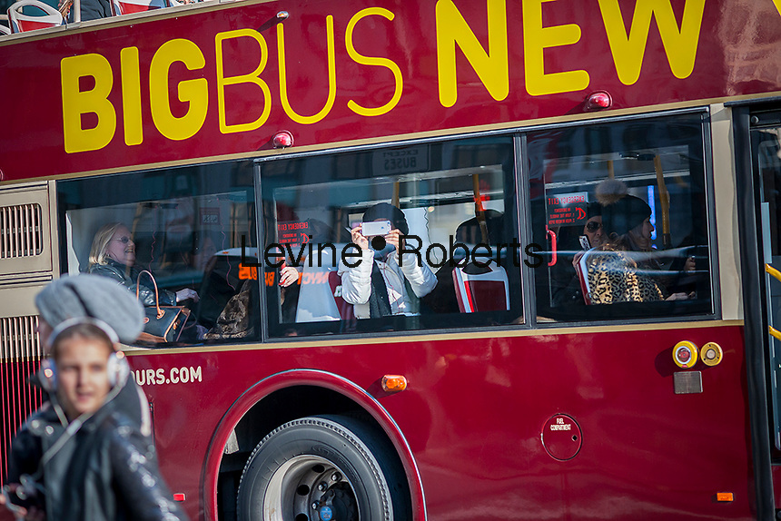A women videos with her iphone on a tour bus shepherding tourists around New York on Friday, December 9, 2016. (© Richard B. Levine)